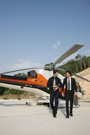 Businessmen walking away from helicopter photo