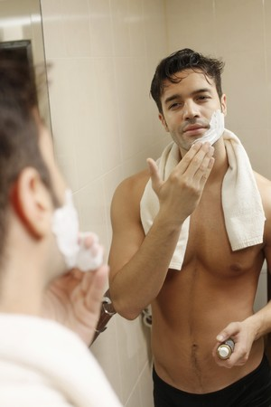 mirror image: Man applying shaving cream Stock Photo
