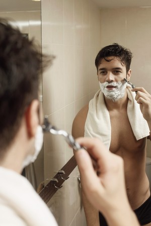 shave: Man shaving in front of mirror Stock Photo