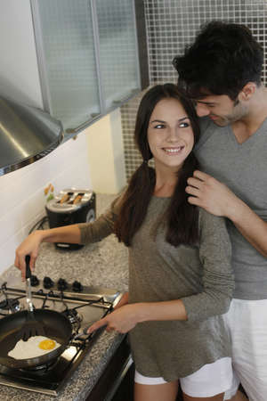 ukrainian ethnicity: Man standing behind woman while she is preparing breakfast in kitchen Stock Photo