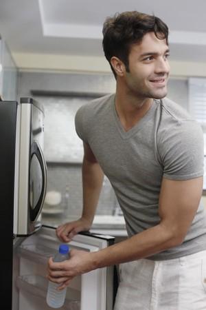 tomando refresco: Hombre tomando agua de botella del refrigerador  Foto de archivo