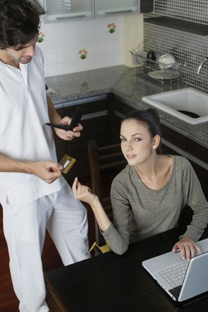 Man giving credit card to woman for online shopping photo