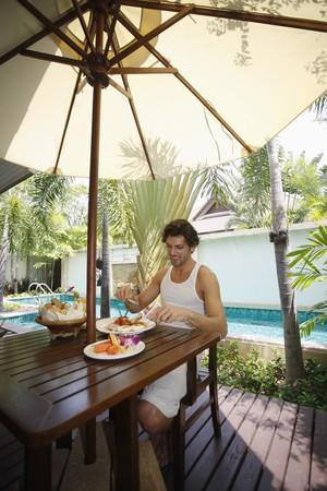 Man having breakfast by the pool Stock Photo - 7361001