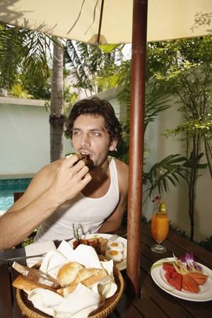 Man having breakfast by the pool Stock Photo - 7360901