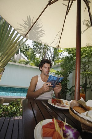 Man reading book with breakfast on the table Stock Photo - 7360929