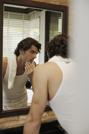 mirror image: Man examining himself in front of the mirror