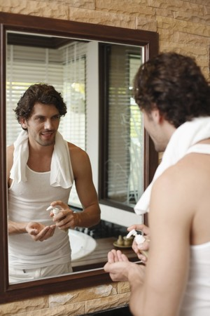 Man looking at reflection in the mirror, about to wash up photo