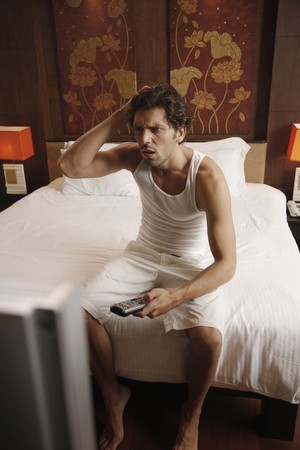 Man watching television with hand in hair Stock Photo - 7360767