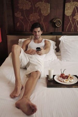 Man watching television with breakfast on bed Stock Photo - 7360718