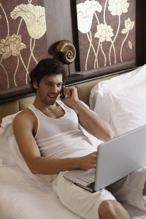 Man using laptop while talking on the phone Stock Photo - 7360958