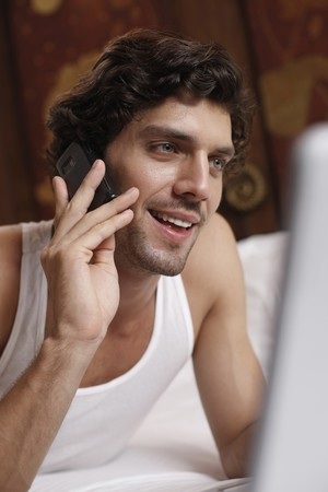 Man using laptop while talking on the phone Stock Photo - 7359303
