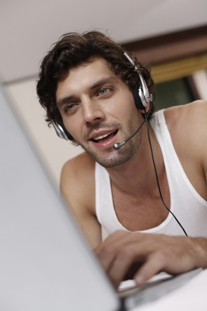 Man with headset using laptop photo