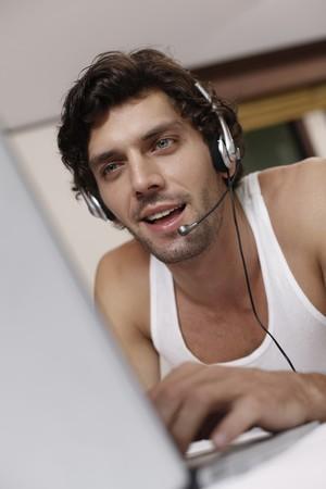turkish ethnicity: Man with headset using laptop