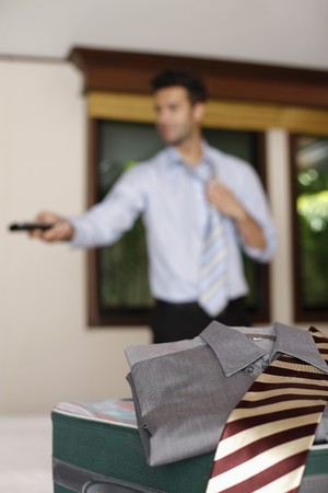 Businessman with remote control, loosening his tie Stock Photo - 7359196