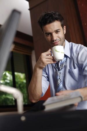 tomando refresco: Libro de toma de empresario de malet�n mientras bebe caf�  Foto de archivo