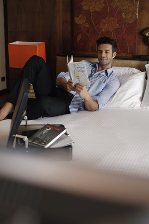 Businessman reading book on bed Stock Photo - 7360382