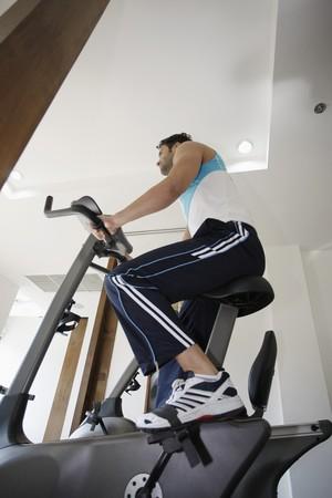Man on exercise bike at gym photo