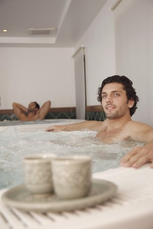 southeastern european descent: Men relaxing in hot tub, tea cups in the foreground