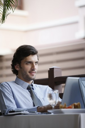 Businessman working while having lunch at restaurant photo