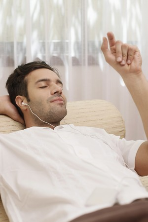 Man listening to music on portable mp3 player Stock Photo - 7359022