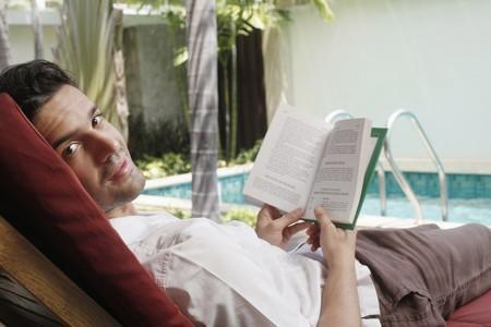 southeastern european descent: Man reading book on lounge chair