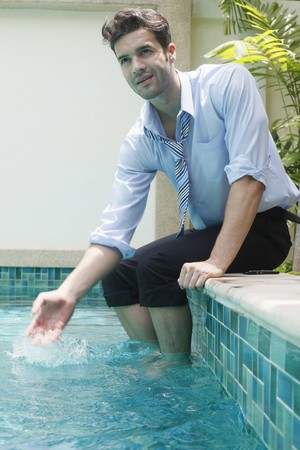 Businessman with feet in swimming pool, splashing water Stock Photo - 7360899