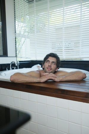 Man daydreaming while in bubble bath photo