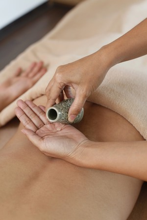 Massage therapist applying therapeutic oil on man photo