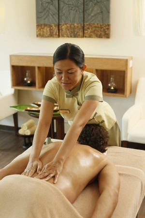 Massage therapist massaging mans back photo