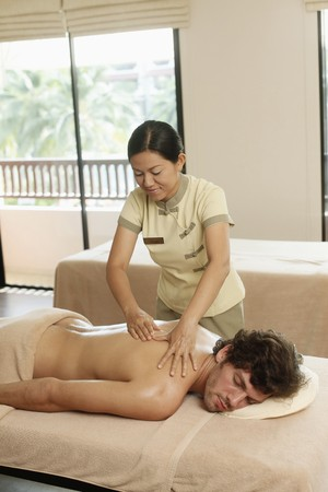 Massage therapist massaging mans back photo