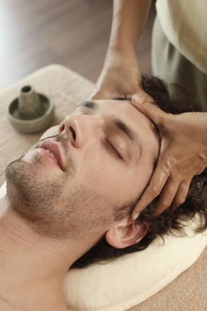 Massage therapist massaging mans head photo