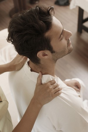 southeastern european descent: Massage therapist massaging mans shoulders