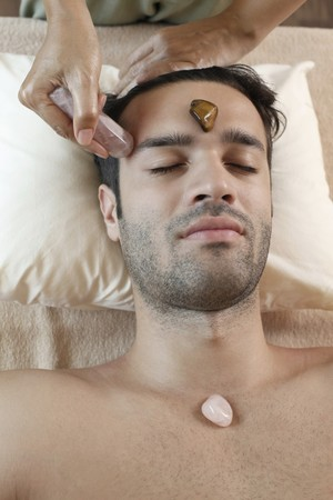 Man receiving crystal healing treatment photo