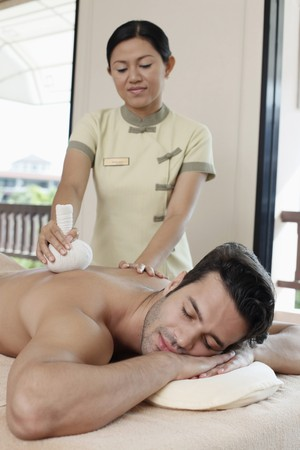 Man receiving a herbal pack massage from a massage therapist photo