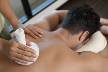 Man receiving a herbal pack massage from a massage therapist