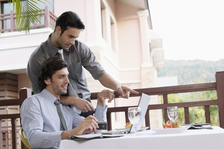 Businessmen looking at laptop photo