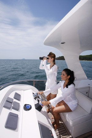 Woman steering yacht while another woman is looking through binoculars Stock Photo - 7362003
