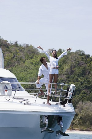 Man and woman standing at the tip of yacht, woman with arms raised Stock Photo