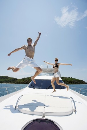 Couple jumping with arms raised on yacht Stock Photo - 7361901