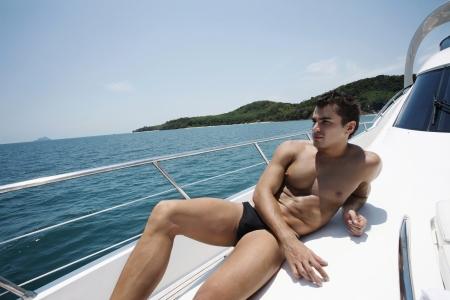 russian man: Man in swimwear relaxing on yacht Stock Photo