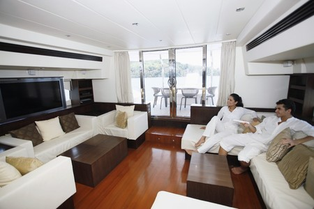 Couple watching television in yacht living room Stock Photo - 7362274