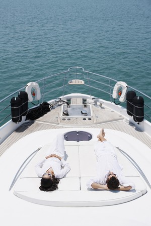Couple sunbathing on yacht deck photo