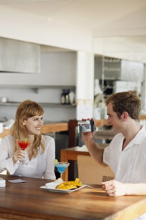 australian ethnicity: Man using video camera to record woman holding cocktail drink Stock Photo