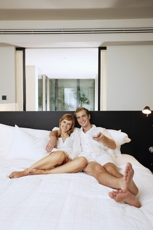 Couple relaxing while watching tv in resort bedroom photo