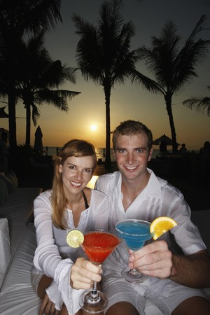australian ethnicity: Couple toasting cocktail during sunset