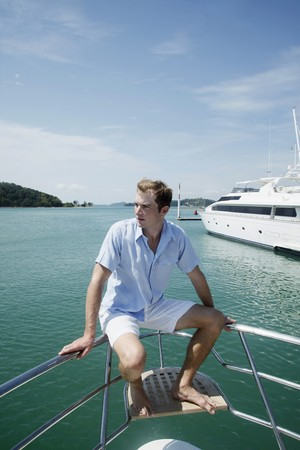 australian ethnicity: Man sitting on railing at the tip of the yacht