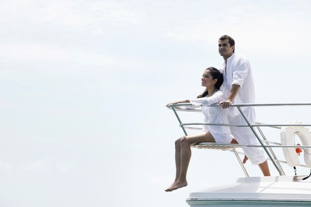 Couple relaxing at the tip of the yacht Stock Photo - 7361789