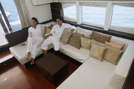 luxury yacht: Couple relaxing in yacht living room Stock Photo