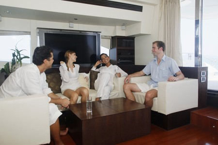 Couples relaxing in yacht living room photo