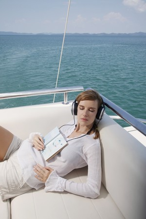 Woman listening to music with book on her body photo
